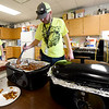 Branco volunteer Dustin Branham stirs chili for nachos as Lakin Larimore looks on in one of four hospitality rooms during the 2018 Neosho Holiday Classic on Thursday afternoon at NHS. More than 40 volunteers help feed players, coaches, media and officials after each game in the tournament.<br /> Globe | Laurie Sisk