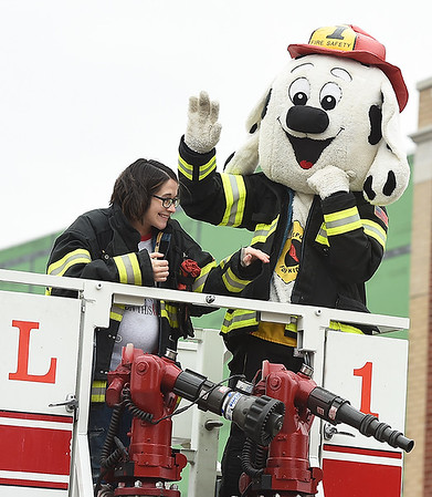 Representatives, including a fire safety mascot, wave from the top of a Galena Fire Department truck during the Baxter Springs Christmas Parade on Saturday in downtown Baxter Springs. Globe | Laurie Sisk