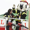 Representatives, including a fire safety mascot, wave from the top of a Galena Fire Department truck during the Baxter Springs Christmas Parade on Saturday in downtown Baxter Springs.<br /> Globe | Laurie Sisk