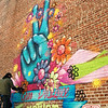 Daniel Gulick works on a mural on the side of the Columbia Traders building on Monday afternoon. Gulick created the mural with fellow Tulsa artist Tony Carrera in partnership with TOMS shoes. The company is sponsoring a nation-wide campaign to create murals to end gun violence.<br /> Globe | Roger Nomer