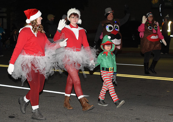Festively clad marchers make their way down Main Street during the 2018 Christmas Parade on Tuesday night in Downtown Joplin.<br /> Globe | Laurie Sisk