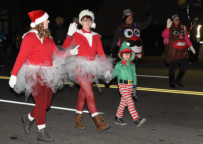 Festively clad marchers make their way down Main Street during the 2018 Christmas Parade on Tuesday night in Downtown Joplin. Globe | Laurie Sisk