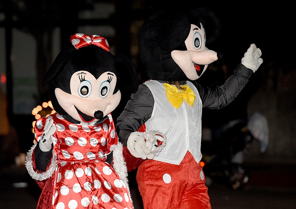 Minnie and Mickey Mouse walk hand-in-hand down the parade route during the 2018 Christmas Parade on Tuesday night in Downtown Joplin.<br /> Globe | Laurie Sisk