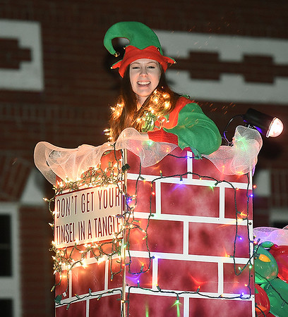 An elf pops up from a chimney on a float during the Neosho Christmas Parade on Saturday night in downtown Neosho.<br /> Globe | Laurie Sisk
