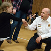Dustin Lunow, Joplin Fire Department assistant fire chief, talks with Kinlea King, 2, on Tuesday at the annual Christmas for Kids event at Joplin Memorial Hall. <br /> Globe | Roger Nomer