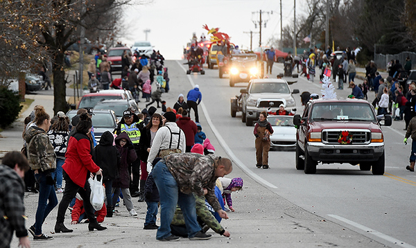 Galena Parade goers scramble for candy during the Galena Christmas Parade on Saturday in downtown Galena.<br /> Globe | Laurie Sisk