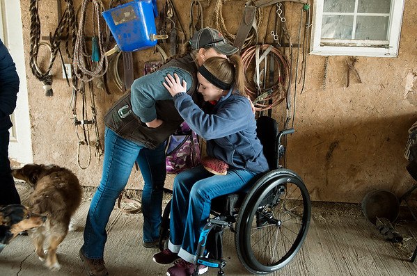 Kelly Gregory gives a welcoming hug to Sami Bayless at her farm in Lamar on Wednesday. While Bayless has been recovering from her car accident, Gregory has taken care of her horse Dunny.<br /> Globe | Roger Nomer