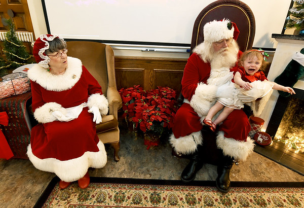 One-year-old Addison Jones expresses more than a little intrepisation as she makes her first visit with Santa during the City of Pittsburg's Christmas celebration on Thursday at Pittsburg City Hall. In addition to visits with Santa, chikdren were given small gifts and candy canes.<br /> Globe   Laurie Sisk