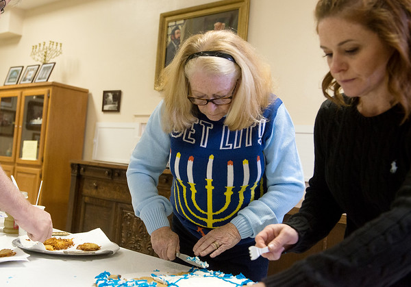 Jane, left, and Rhea Brown prepare food for the Hanukkah celebration on Sunday at the United Hebrew Congregation Temple.<br /> Globe | Roger Nomer