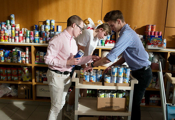 (from left) Thomas Jefferson Independent Day School juniors Preston Johnson, Brock Conklin and Luke Goodhope load donated canned goods to give to the Salvation Army on Tuesday.<br /> Globe | Roger Nomer