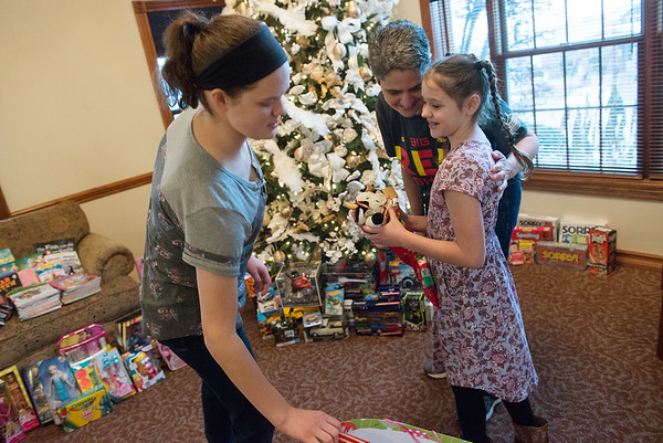 (from left) Amber, Jodi and Hannah Helwig prepare gifts at the Ronald McDonald House on Tuesday, Dec. 13.<br /> Globe | Roger Nomer