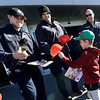 From the left: Joplin firefighters Dakota Triplett, Adam Stewart and John Hubbard give 8-year-old Jay Studyvin a helmet and coloring book as they ring the bells for the Salvation Army kettle on Saturday at Walmart on 15th and Range Line. Joplin Police officers also donated their time on Saturday to help the Salvation Army meet its fundraising goal.<br /> Globe | Laurie SIsk