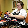 Homewood Suites employee Edie Chandler joins a small army of volunteers as they tag new scarves, hats and gloves for distribution throughout the Joplin community as part of the Chase the Chill program. Volunteers will distribute more than 1,000 items as part of the program, which is in its fourth year.<br /> Globe | Laurie Sisk