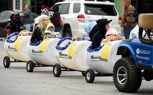 The Cherokee County Sheriffs Department pulls riders down Military Avenue in a train made of plastic barrels during the Baxter Springs Christmas Parade on Saturday in downtown Baxter Springs.<br /> Globe | Laurie Sisk