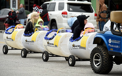 The Cherokee County Sheriffs Department pulls riders down Military Avenue in a train made of plastic barrels during the Baxter Springs Christmas Parade on Saturday in downtown Baxter Springs. Globe | Laurie Sisk