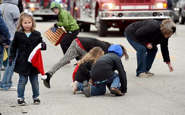 Children scramble for candy during the Baxter Springs Christmas Parade on Saturday in downtown Baxter Springs.<br /> Globe | Laurie Sisk