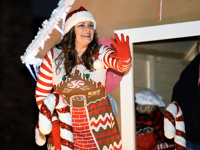 A woman waves from a gingerbread house during the Neosho Christmas Parade on Saturday night in downtown Neosho. Globe | Laurie Sisk