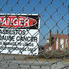 A sign warning people about the dangers of asbestos exposure hangs on a fence in the foreground of the old B.F. Goodrich powerhouse, which still contains asbestos around copper pipes.<br /> Globe | Laurie Sisk