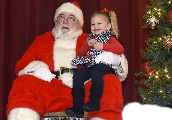 Three-year-old Nora Gilleland smiles for a photo with Santa during Breakfast with Santa on Saturday morning at the Neosho Civic Center.<br /> Globe | Laurie Sisk