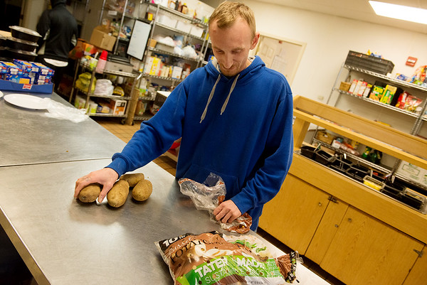 Sean Krzyzanowski prepares potatoes for a Christmas party at the Carthage Crisis Center on Wednesday.<br /> Globe | Roger Nomer