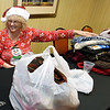 Cindy King helps tag new scarves, hats and gloves for distribution throughout the Joplin community as part of the Chase the Chill program on Thursday night at Homewood Suites. King and seven other members of Hands of Love knitted 147 hats and 47 scarves for the program, which will distribute more than 1,000 items.<br /> Globe | Laurie Sisk