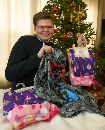 Easton Murdock holds some of the pajamas he hands out to children's hospitals in numerous states. To date, Murdock has delivered about 5,000 pajamas to hospitalized children.<br /> Globe   Laurie Sisk