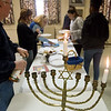 A Menorah is lit during a Hanukkah celebration at the United Hebrew Congregation Temple on Sunday.<br /> Globe | Roger Nomer