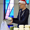 Christian Willoughby helps pack meals for delivery during the First Christian Church's Christmas dinner on Tuesday at the church.<br /> Globe | Laurie Sisk