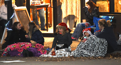 Spectators enjoy warm drinks, blankets and conversation as they await the start of the 2018 Christmas Parade on Tuesday night in Downtown Joplin. Globe | Laurie Sisk
