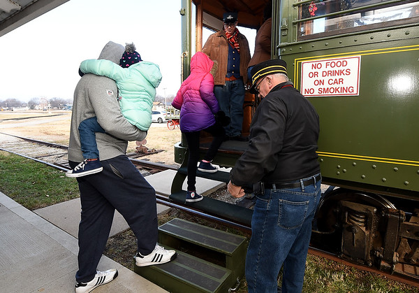 Conductors Chuck Edds (top) and Clyde Thornburg, right, assist passesngers as they board the Polar Express on Saturday at the Webb City Farmers Market. Free rides on the train continue next Saturday from 9 a.m. to noon.<br /> Globe | Laurie Sisk