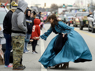 Brittany Odom, of the United Daughters of the Confederacy, hands candy to kids during the Baxter Springs Christmas Parade on Saturday in downtown Baxter Springs. Globe | Laurie Sisk