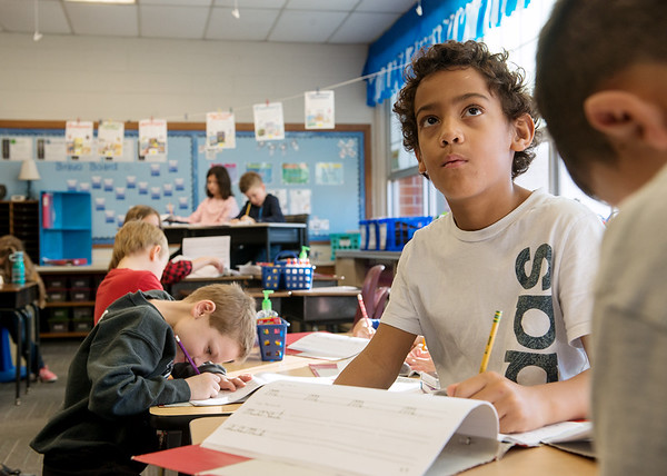 Kobe Hayes checks examples of cursive letters during class in third grade at Kelsey Norman Elementary on Thursday.<br /> Globe   Roger Nomer