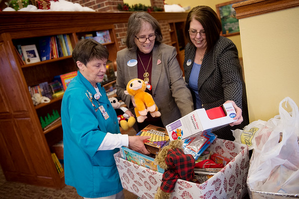 (from left) Susan Carlsten, president of the Freeman Auxiliary, Shirley Hylton, program coordinator for the Ronald McDonald House of the Four States, and Jerri Sargent, house program manager, look over toys donated to the house by the auxiliary on Tuesday. These toys will be given to current and past families who have stayed at the house to provide for Christmas gifts.<br /> Globe | Roger Nomer