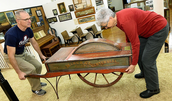 From the left: Granby Miners Museum President Steve Burnett and his wife, museum volunteer Jann Burnett, move an historic wheelbarrow from its perch at the museum on Tuesday.<br /> Globe | Laurie Sisk