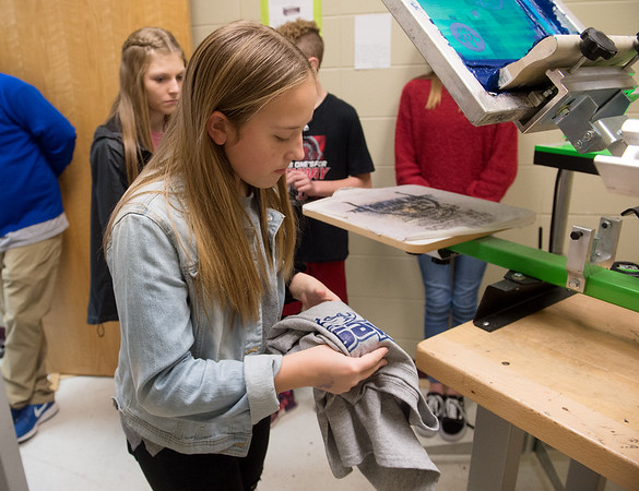 Lucy Erisman, seventh grader at South Middle School, helps fold shirts for Eagle Threads on Friday.<br /> Globe | Roger Nomer