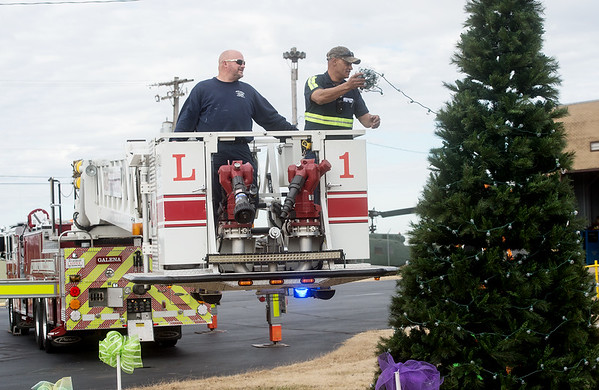 Chad Stapleton, lieutenant with the Galena Fire Department, left, gives David Berry, maintenance with the City of Galena, an assist in hanging Christmas tree lights at Galena City Hall on Thursday. Lighting of the tree will take place on Saturday immediately after the city's Christmas parade.<br /> Globe | Roger Nomer