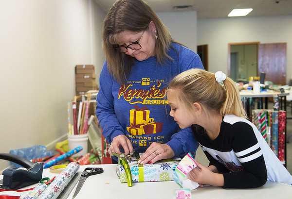 Corabelle Haley, 5, watches her grandmother Bellaree Blackford wrap a gift on Tuesday as part of Kenzie's Kruisers annual Wrapping for the Cystic Fibrosis Cure. The organization will wrap gifts from now through Christmas Eve for a suggested donation to the Cystic Fibrosis Foundation. The event is in its 11th year and is located at 2404 Grand Avenue in Carthage.<br /> Globe   Roger Nomer