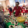 Faustina Abrahams tops off David Dailey's dessert on Wednesday at the annual Christmas meal at First Community Church in Joplin.<br /> Globe | Roger Nomer