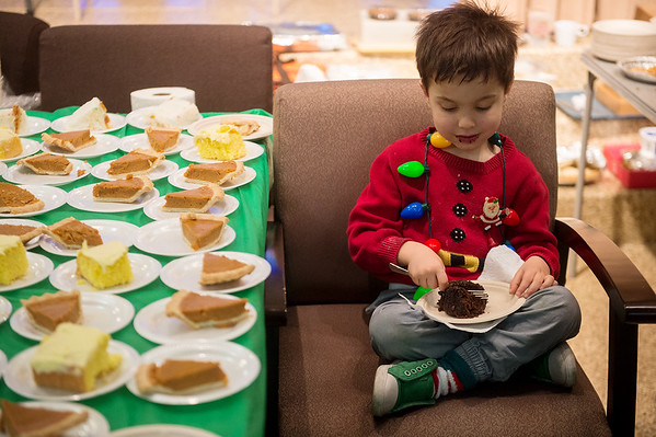 Asher Cullers, 4, takes a dessert break while helping his mother on Wednesday at the annual Christmas meal at the First Community Church in Joplin.<br /> Globe | Roger Nomer