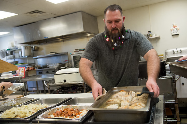 Jared Oxford, assistant director of the Carthage Crisis Center, sports a festive beard as he helps set up for the Christmas meal at the center on Wednesday.<br /> Globe | Roger Nomer