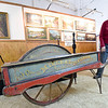 Granby Miners Museum  volunteer Jann Burnett stands near the centennial wheelbarrow near its perch at the museum on Tuesday.<br /> Globe | Laurie Sisk