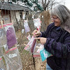 Pam Parcell puts stocking caps on her fence at 9th and Ohio in Joplin on Friday morning.<br /> Globe | Roger Nomer