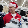 Donovan Edwards, senior manager of shared services for CFI, shops for a family during Thursday's Truckloads of Treasure holiday shopping spree at Walmart. CFI employees purchased gifts for 300 local families after they raised over $41,000 for the annual giving event. Checks were also presented to several local charities.<br /> Globe | Roger Nomer