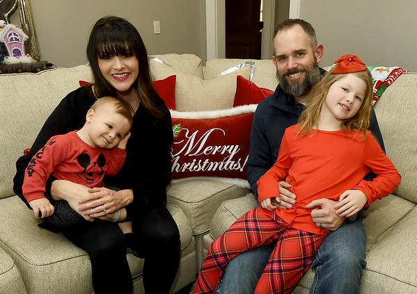 The Asbell family sit in the living room in their Carl Junction home. The family has devoted each Christmas for the past six years into giving to others in the community.<br /> Globe | Laurie Sisk