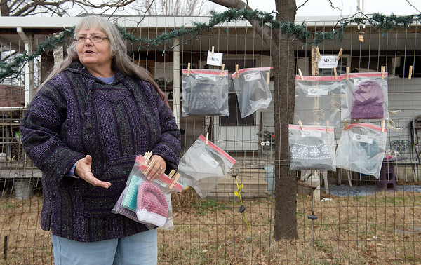 Pam Parcell talks about how she started putting crocheted clothing items on her fence at 9th and Ohio on Friday.<br /> Globe | Roger Nomer