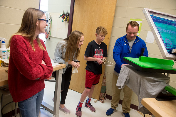 Patrick Bromley, industrial technology teacher at South Middle School, helps seventh graders (from left) Lily Breidenstein, Lucy Erisman and Kutler Schwarting with a screen print on Friday.<br /> Globe | Roger Nomer