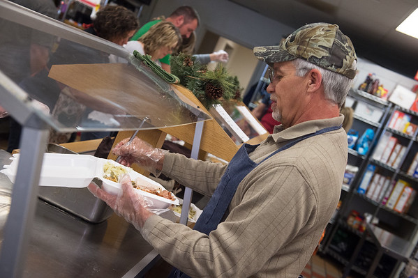 Erwin Frazier, Carthage, helps assemble a delivery meal as he volunteers on Wednesday at the Carthage Crisis Center.<br /> Globe | Roger Nomer