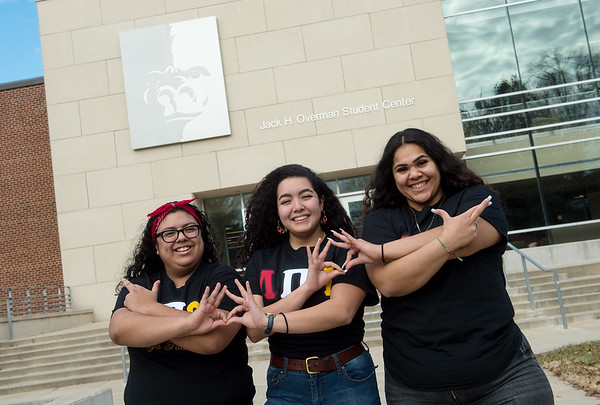 (from left) Natalie Vasquez, a Pittsburg State University junior from Kansas City, Kan., Cassandra Roque, a PSU senior from Westwood, Kan., and Samantha Ruvalcaba, a PSU junior from Wichita, Kan., show the sign for Lambda Pi Upsilon Sorority on Thursday. The students are the first members of the new sorority on campus.<br /> Globe | Roger Nomer