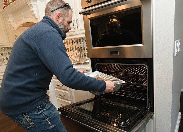 Jake Asbell places a pecan pie in the oven  for their annual community Christmas dinner at the Carl Junction Community Center.<br /> Globe | Laurie Sisk
