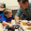 Walter Fuchs, 4, makes seed balls with John Fenton, with the CJ Cultivators, on Friday at the Footprints and Friends Preschool.<br /> Globe | Roger Nomer